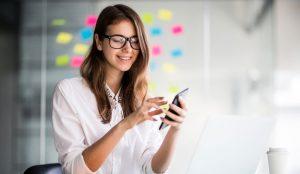 Una mujer joven con gafas usando un teléfono inteligente.