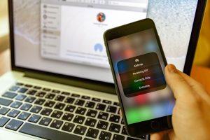 Configuración de AirDrop en un iPhone con una MacBook en segundo plano.
