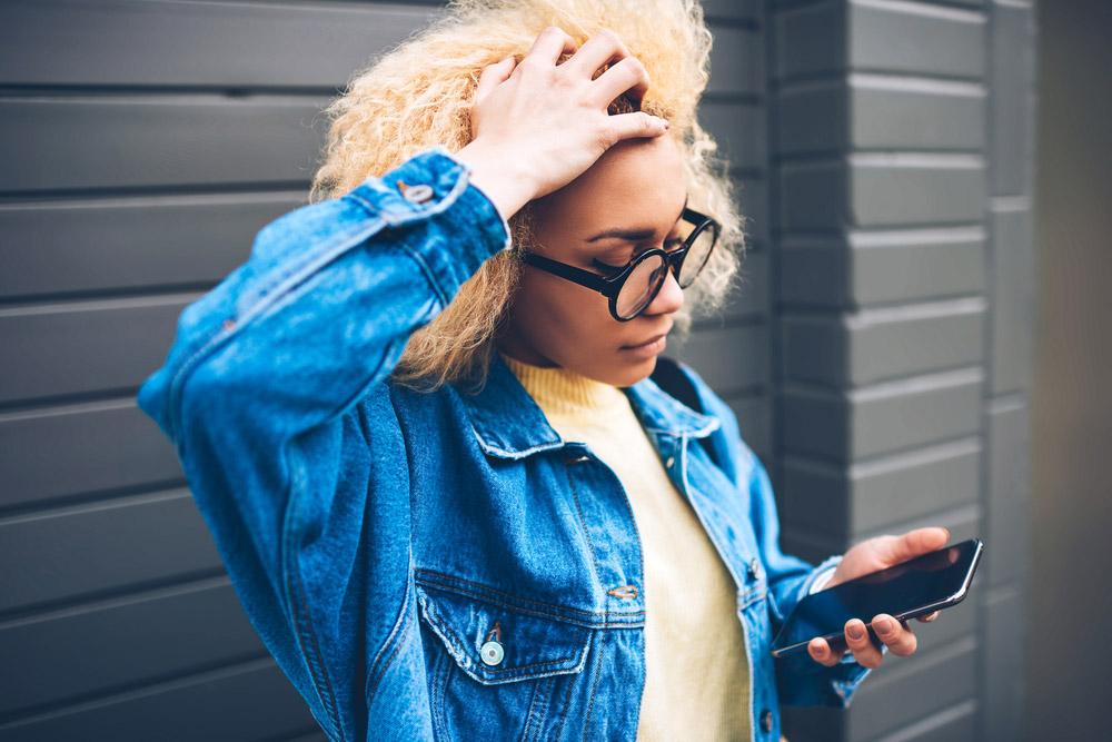 Mujer joven mirando el teléfono y agarrando el cabello con frustración.