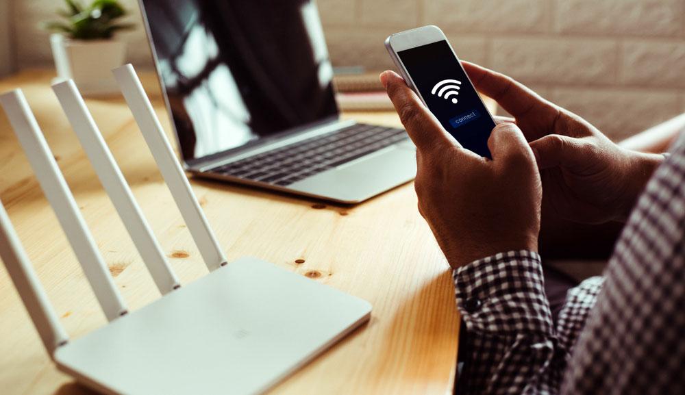 Un hombre usa un teléfono inteligente para conectarse a una red Wi-Fi, con un enrutador y una computadora portátil en un escritorio.
