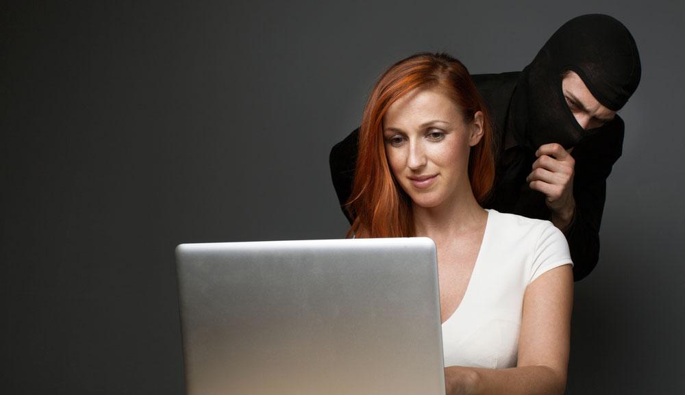 La mujer blanca pelirroja escribe en la computadora portátil mientras una figura amenazadora con pasamontañas mira sobre su hombro.