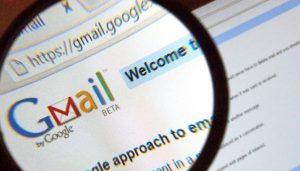 El logotipo de Gmail en la pantalla de una computadora bajo una lupa.